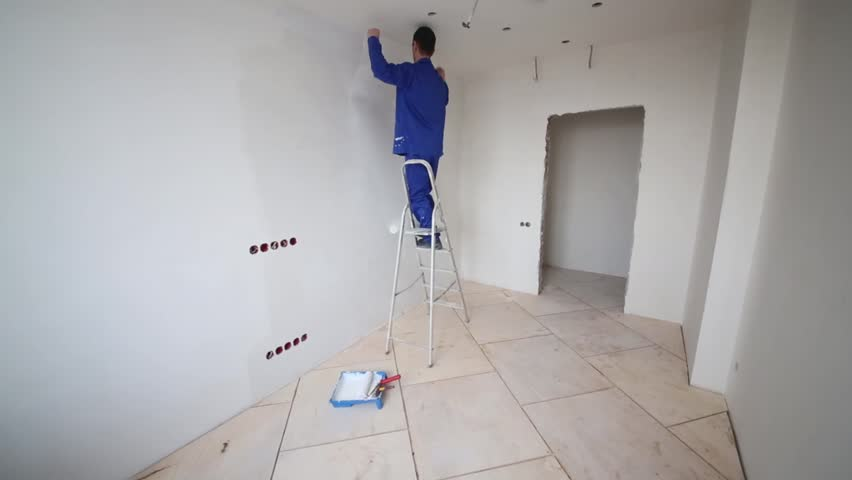 Worker standing on a ladder and puts fiberglass to the wall in an empty room - HD stock video clip