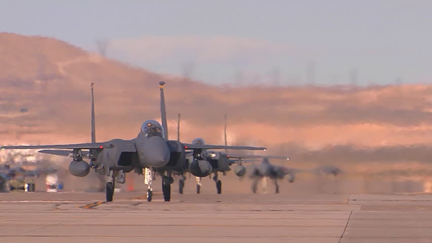 CIRCA 2010s - F-15 and F-16 fighter jets line up and taxi for takeoff in a military exercise.