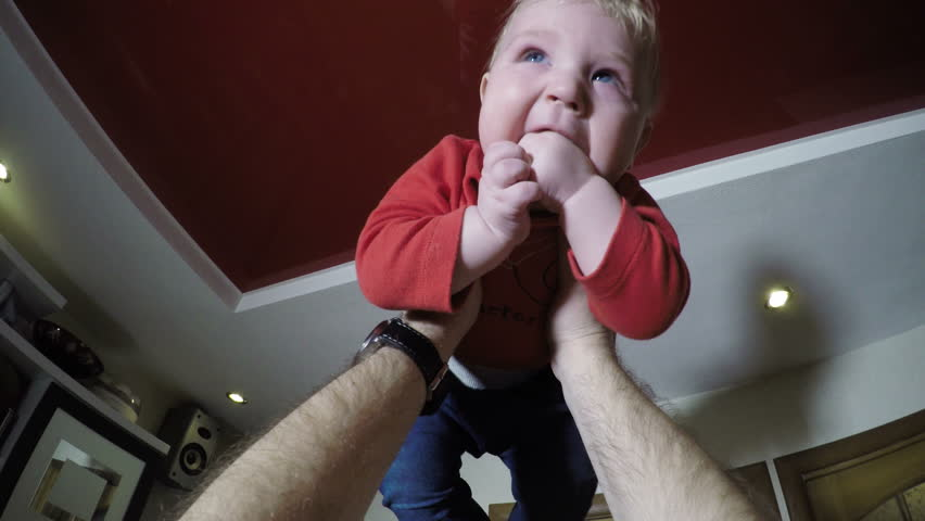 father lifts baby in kitchen pov - 4K stock video clip
