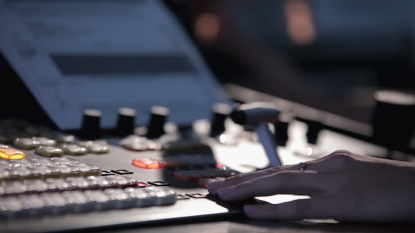 Television director during the live broadcast, switches cameras in the studio. Pushes the handle console in mobile television station telecruiser.