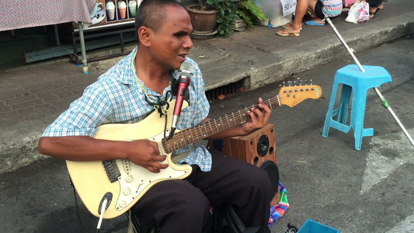 Bangkok, Thailand - March 2015 : Blind artist playing electric guitar with mini speaker on street for some moeny from tourist - HD stock footage clip