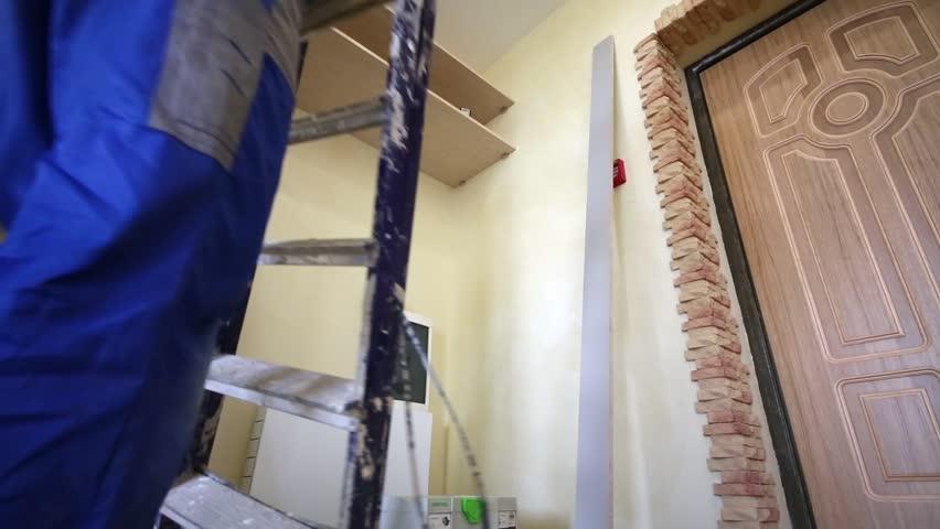 Worker puts stepladder near to niche where sliding door wardrobe mounting. - HD stock video clip