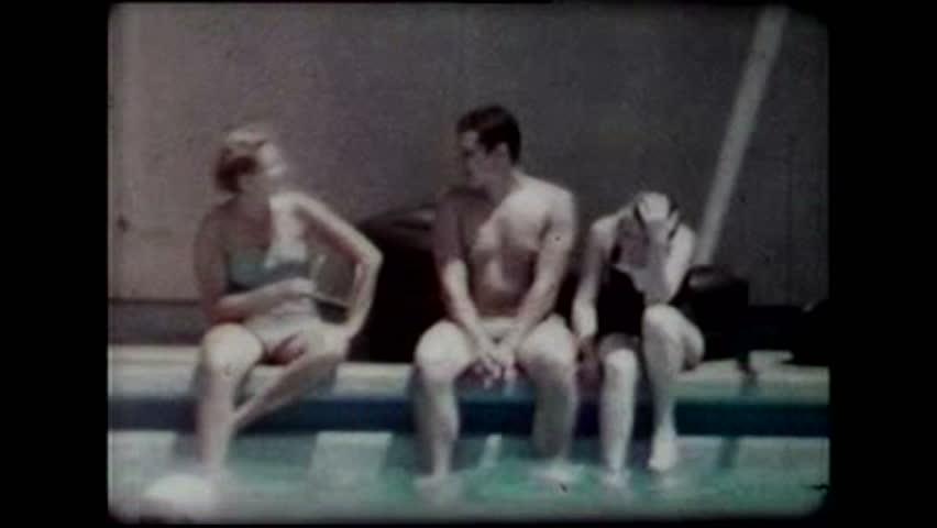 Cincinnati, 1950's. A young woman and a young man sit on the edge of the pool with their feet in the water and talk. A third youngster looks on. - HD stock footage clip