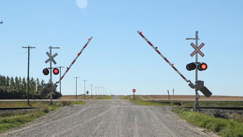 Rail crossing with sound of train coming. Gates lowering. Rail crossing with sound of freight train coming. Kemnay, Manitoba.