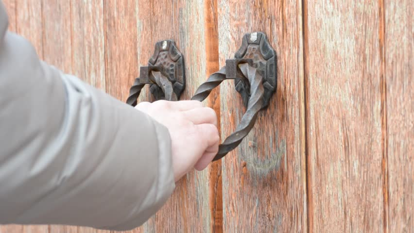 Male Hand Knocking On Old Fashioned Ancient Wooden Gate Or