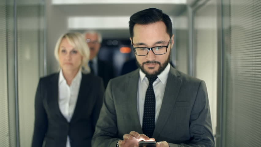 Slow motion of business team approaching camera walking along business center corridor, focus on bearded Asian man with phone