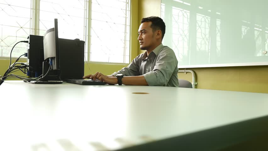 Depressed young employee using computer in the office