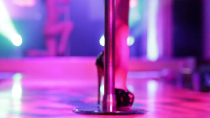 Beautiful legs of woman in high-heeled shoes dancing on a stage in a strip club. - HD stock footage clip