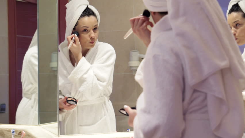 Young woman in bathrobe applying powder on her face with brush in the bathroom  - HD stock footage clip