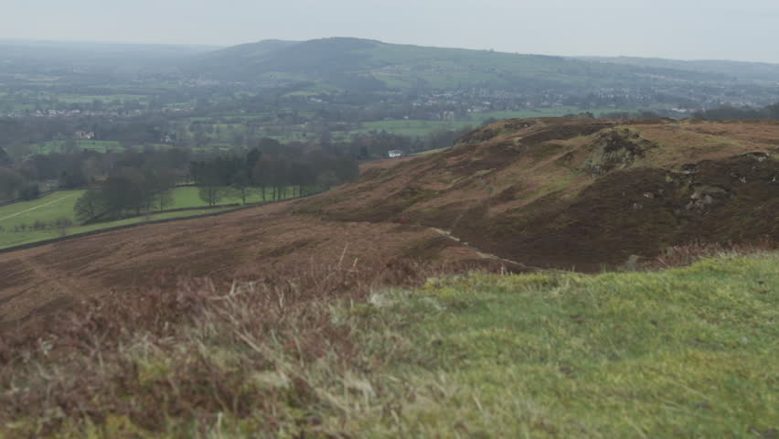Bleak Moorland landscape scene HD stock footage. A beautiful establishing shot of a Yorkshire moor with a person walking up the natural track. Filmed on the BMD Cinema Camera. ProRes 422.