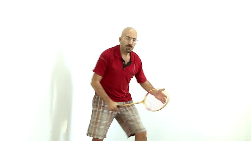 a bald man in a red shirt gets ready to play badminton,tennis,energetically Bouncing and waving his arms and communicates with facial expressions on the face. White flash