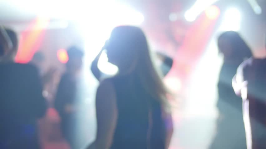 Girl dancing at a concert in slow motion. Blurred picture with plenty of aesthetics.