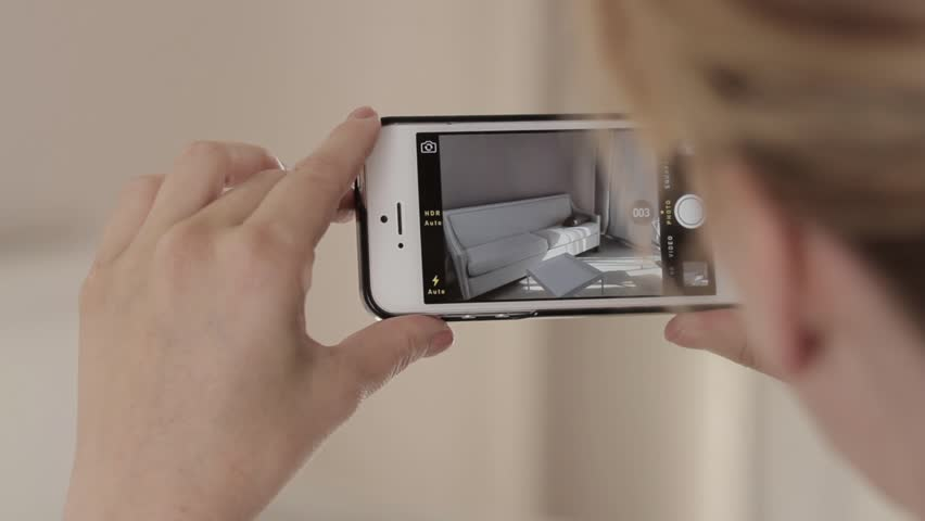 Woman taking a picture of a sofa on a cell phone | Shutterstock HD Video #9335093