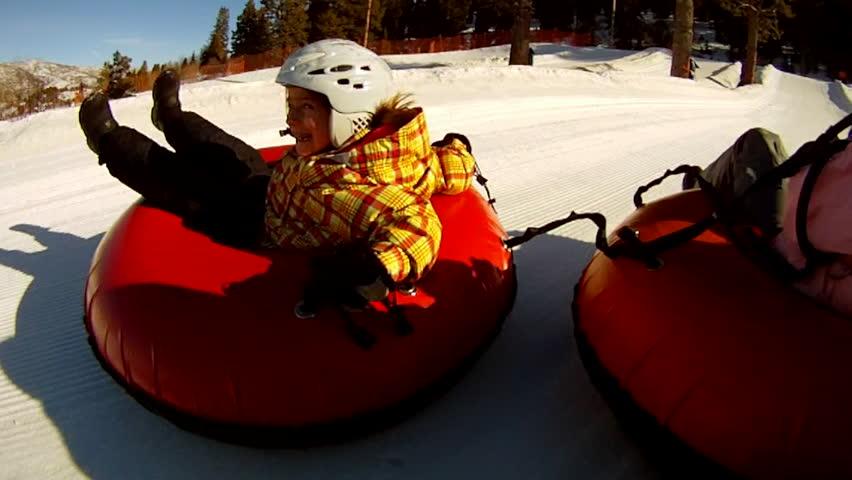 POV of mother, son, and daughter tubing fast down snowy slope.
