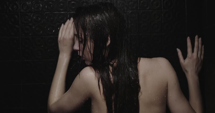Woman taking shower in slow motion. Filmed in 4K DCi resolution. Young sensual woman taking a shower and relaxes under the pouring water. Back view on black background. Beauty and wellbeing concept.