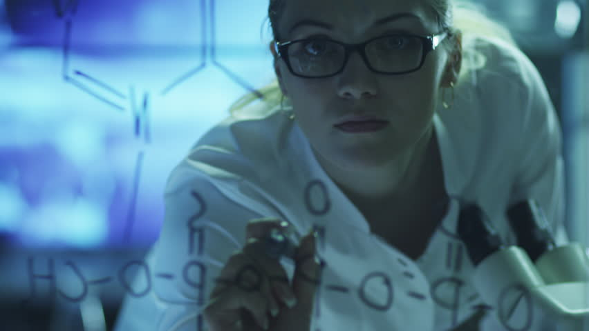 Woman Scientist is Drawing Organic Chemical Formulas on Glass. Shot on RED Cinema Camera in 4K (UHD).