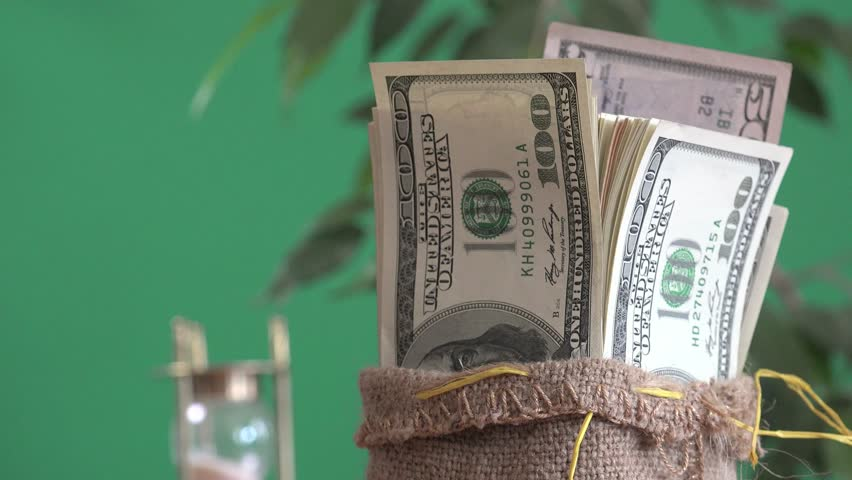 Man's hand takes hundred dollars out of bag, on green background