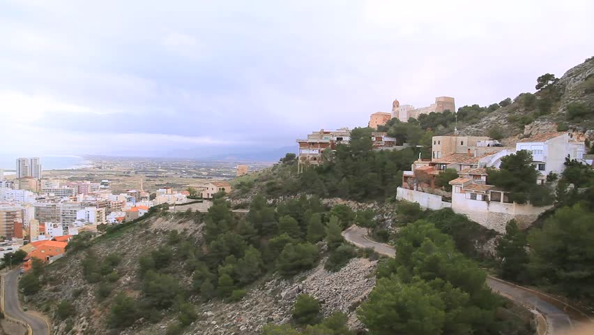 Spain. Cullera town, the view from the mountain on the road serpentine, distant mountains, the distant sea and the medieval castle. rare passing car. winter. - HD stock video clip