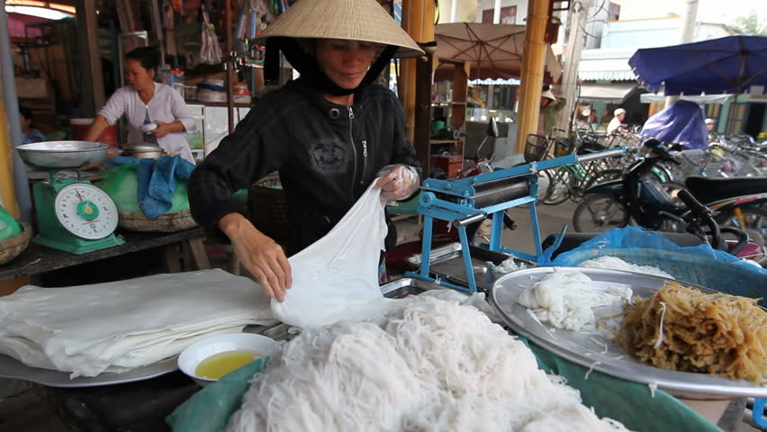 HOI AN, VIETNAM-FEBRUARY 28: A local woman makes rice noodles by hand on February 28, 2010 in Hoi An, Vietnam, a UNESCO world Heritage Site for the preservation of ancient traditions and buildings.  - HD stock footage clip