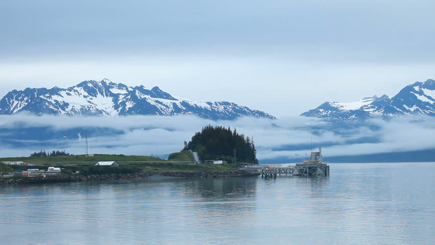 Valdez oil pipeline terminal building. Loading dock where ships are filled for transport of crude oil. Misty fog weather. Glacial snow covered mountains with beautiful clouds. - HD stock footage clip