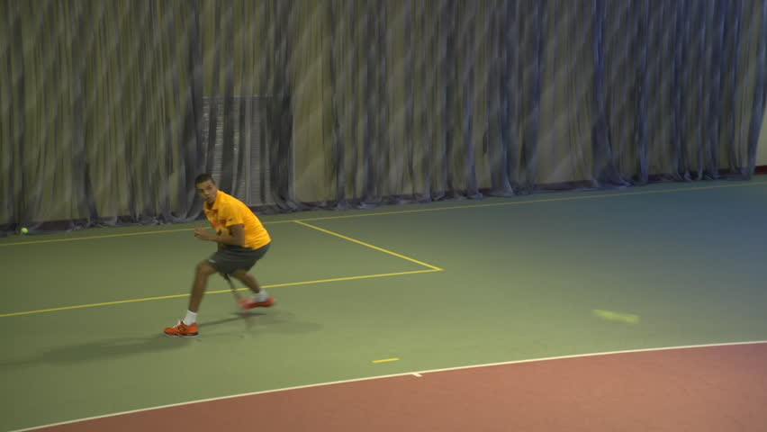Tennis player in action. Moving on the base line. Making powerful shots. Spectacular shot  between  legs
