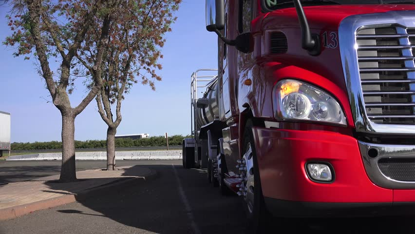 Big rig semi truck low point of view as the truck leaves the truck stop. Truck driving away from a stop. - 4K stock video clip