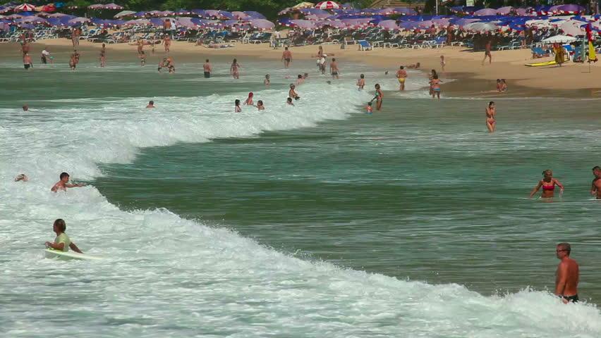 NAI HARN BEACH, PHUKET, THAILAND: NOVEMBER 28, 2011- vacationers people in the waves on the Nai Harn beach - HD stock footage clip