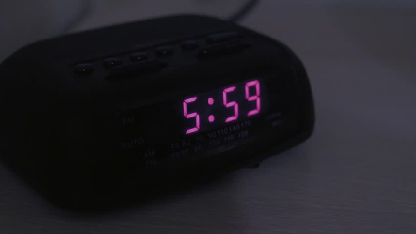 A tired man hits snooze on the alarm clock when it goes off at six o'clock in the morning