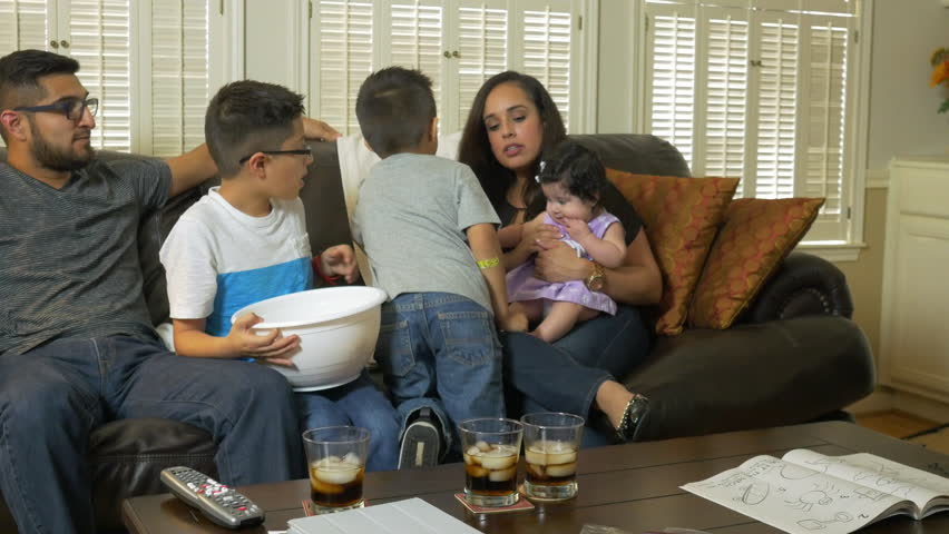 Reveal to a lovely Hispanic family with two cute boys enjoying popcorn as they all sit together ready to watch TV. - 4K stock video clip
