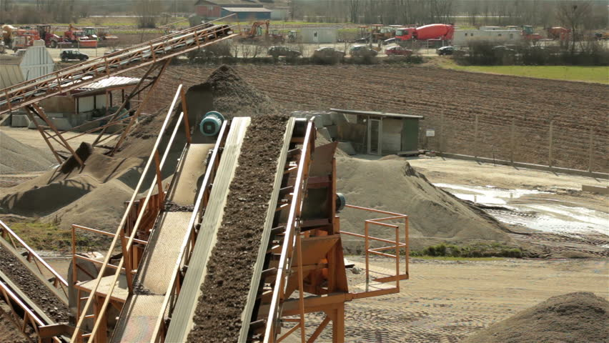 Separation of sand. Sand falling from conveyor belt and forming pile. Yellow excavator (bulldozer) passing by conveyor belts with sand on construction site. Heavy industry. Open pit. High angle view. - HD stock video clip