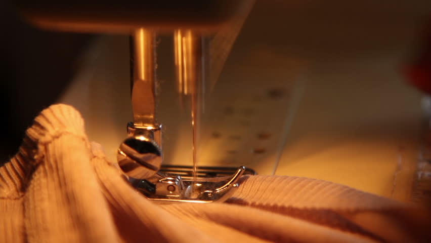 Close up of plate, needle and thread of a sewing machine sewing a fabric