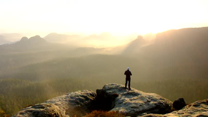 Man takes photos with smart phone on peak of rock empire. Dreamy fogy landscape, spring orange pink misty sunrise in a beautiful valley of Saxony Switzerland park. - HD stock footage clip