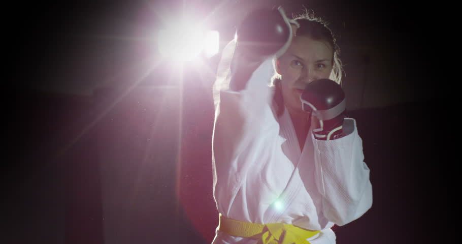 Young female martial artist shadow practicing in slow motion. - 4K stock footage clip