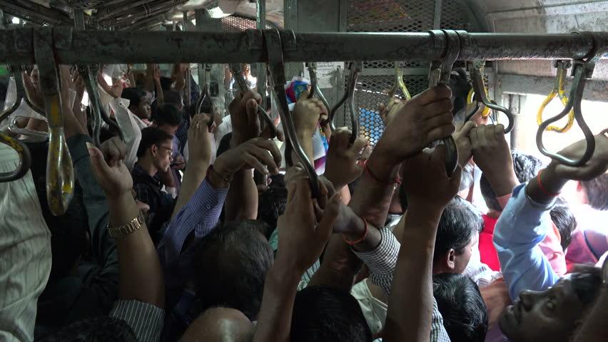 MUMBAI, INDIA - 7 NOVEMBER 2014: People travel on a busy commuter train in Mumbai.