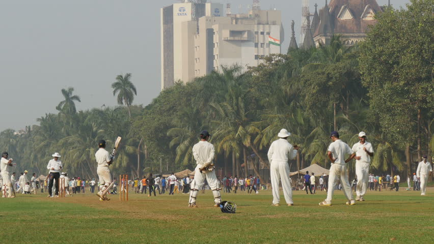 MUMBAI, INDIA - 2 NOVEMBER 2014: People play cricket in front of the Bombay University and a large office building of Tata.