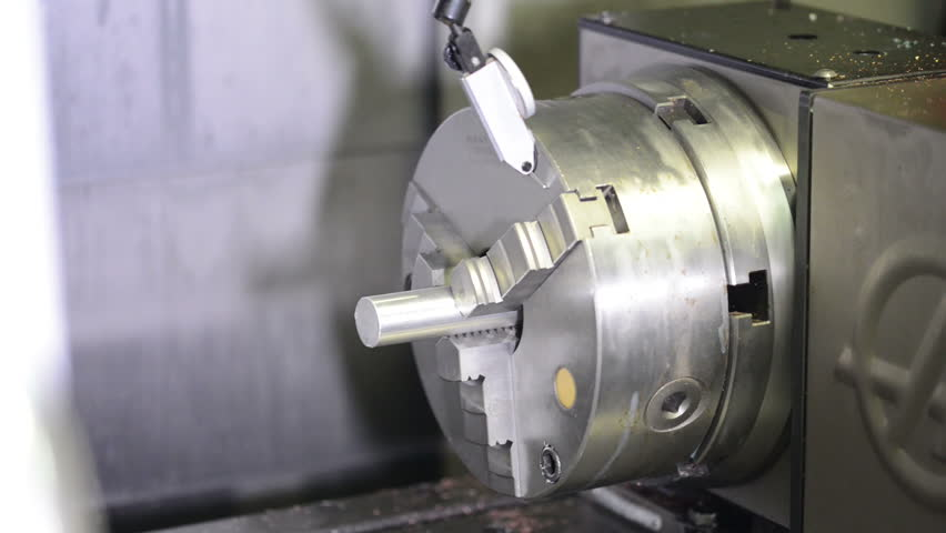 Slide shot of calibrating process of CNC machine with raw metal detail inside the three jaw chuck - HD stock video clip