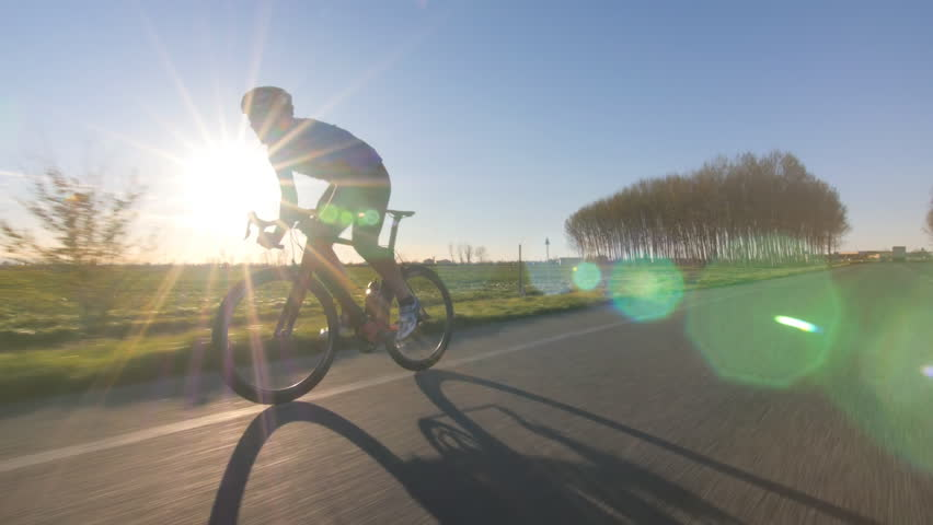 cyclist working out. training fitness outdoors on bike. tracking shot from camera car 4k