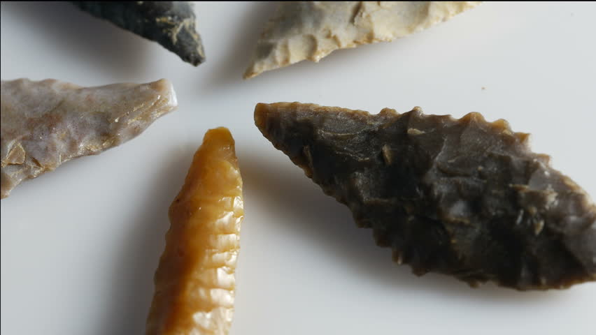 Group of neolithic flint arrowheads rotating 4K, UHD