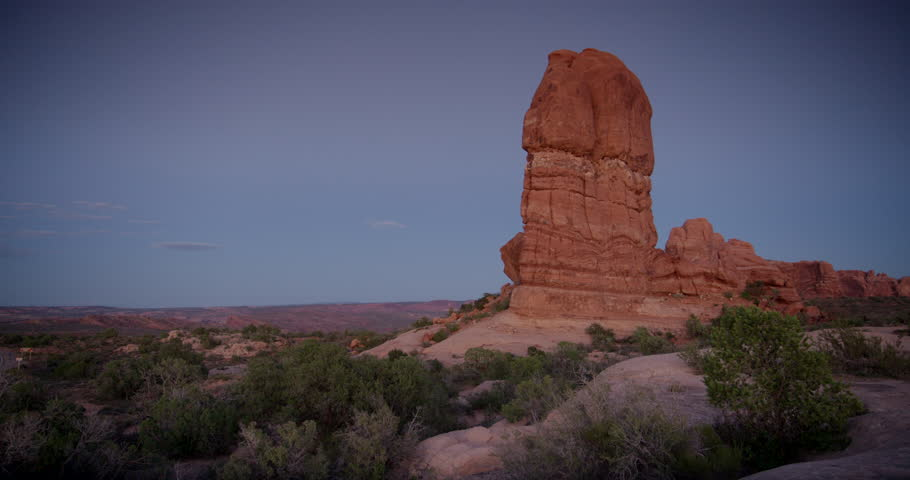 Arches National Park, Moab Utah.  Class C RV motorhome and other cars driving through the desert at sunset.  Camera pans from massive red rock monolith to the road.