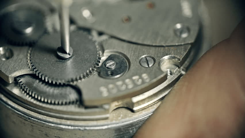 Extreme close up of watch wheel unscrewed and screwed back