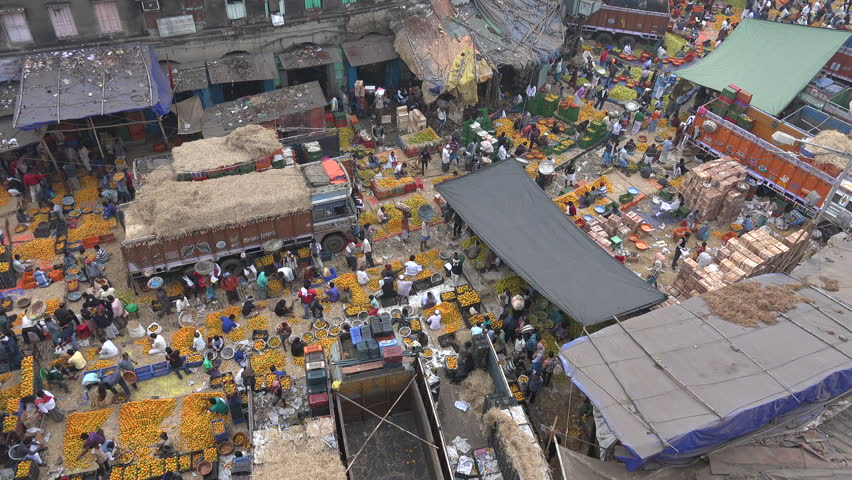 KOLKATA, INDIA - 12 DECEMBER 2014: Overview of a busy wholesale market for fruits and vegetables in Kolkata. In this section people are buying and selling oranges.
