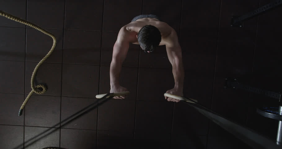 Medium shot slow mo zoom-in, zoom-out young man exercising with gymnastic rings in gym, overhead shot