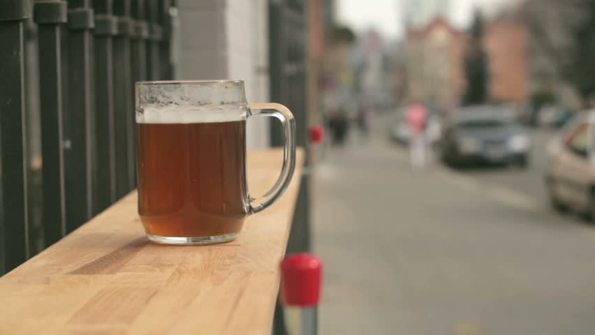 A beer glass on the bar counter near bar with street view on the background