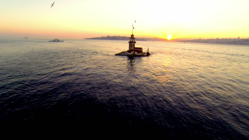 Maidens Tower, Aerial. Flying over Bosporus towards historical lighthouse, Maidens Tower at sunset. High angle view of Istanbul, Turkey.