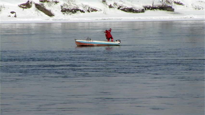 fisherman on a boat in the unfrozen Angara