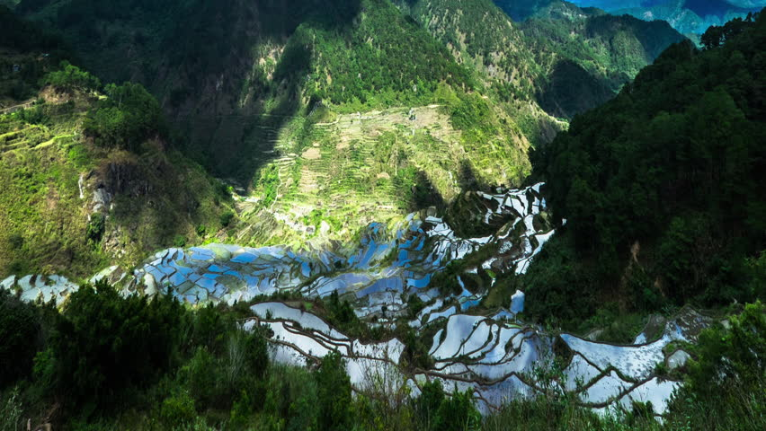 Time lapse of rice terraces fields in Ifugao province mountains with cloudy blue sky reflection in water. Philippines UNESCO heritage