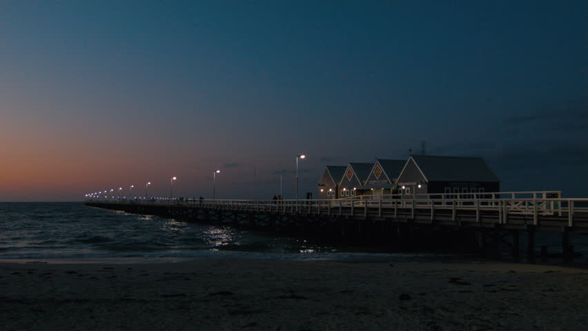 The last light at dusk on the Interpretive Centre and Busselton Jetty in Western Australia. - HD stock video clip