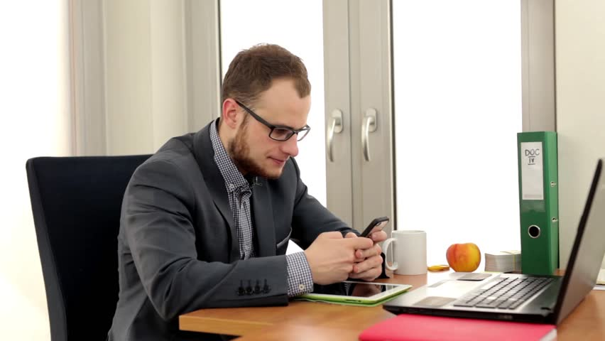 Young, handsome man in suit sitting in the office behind his desk and writing something on the phone, he is looking into the camera. - HD stock footage clip