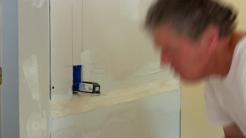 Applying Drywall Tape : Man applies joint compound to drywall seam before applying