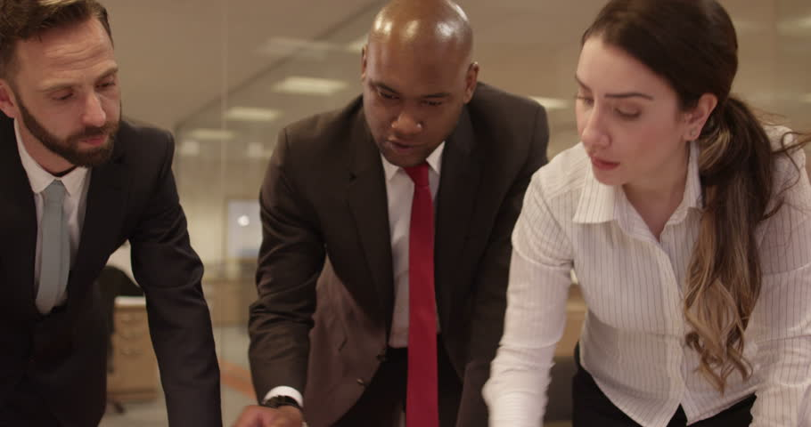 An African American team leader discussing future business ventures with colleagues while looking at a world map. In slow motion.